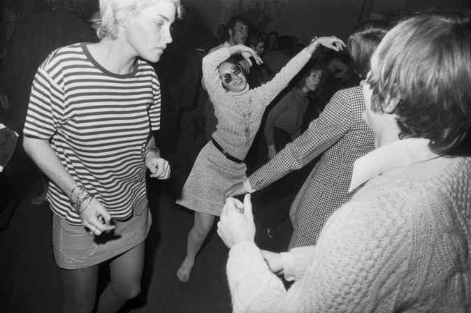 Black-and-white photograph of a woman dancing in a crowd of people