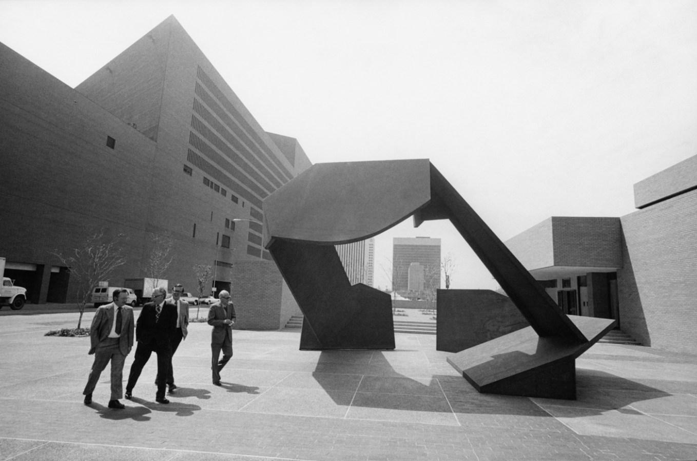 Black-and-white photograph of a group of businessmen passing an empty plaza with a modern geometric sculpture