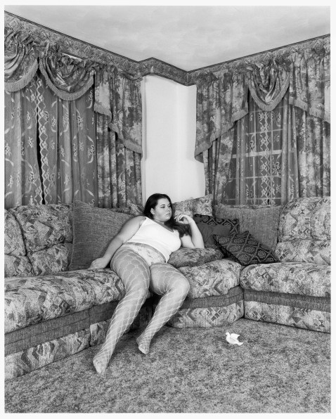 Black-and-white photograph of a woman reclining on an overstuffed corner sofa