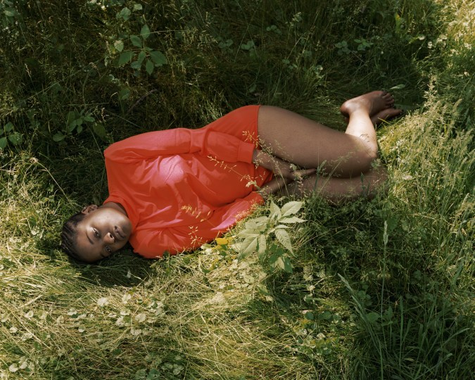 Color photograph of a woman in a red shirt lying on her side in long grass