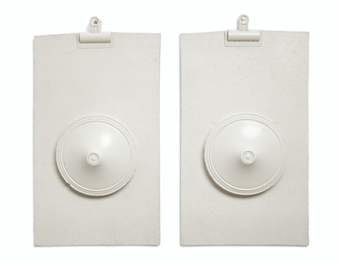 Two all-white sculptures of clipboards with protruding flattened cone forms in the center of each