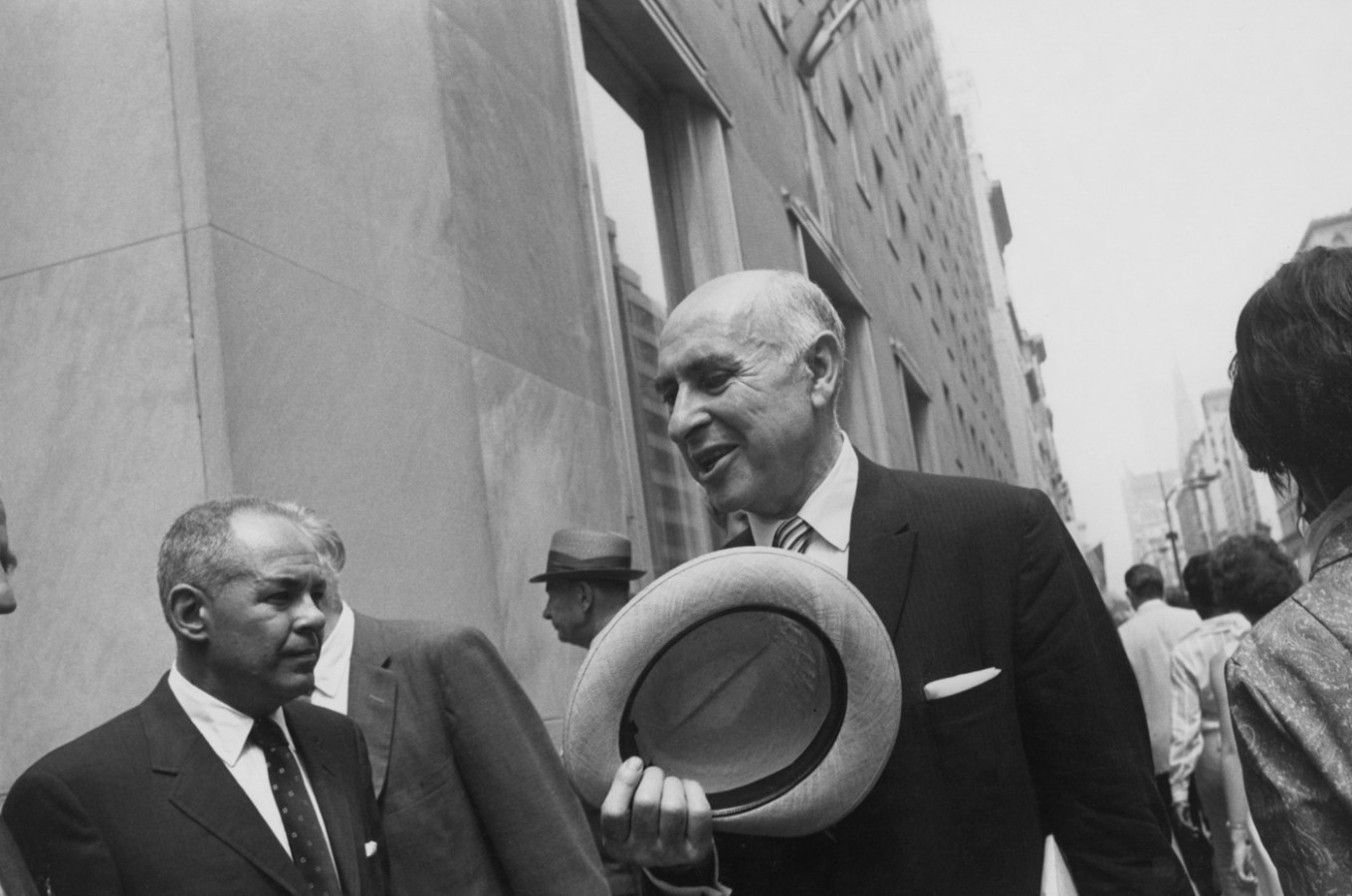Black-and-white photograph of an older balding man in a suit holding a straw hat