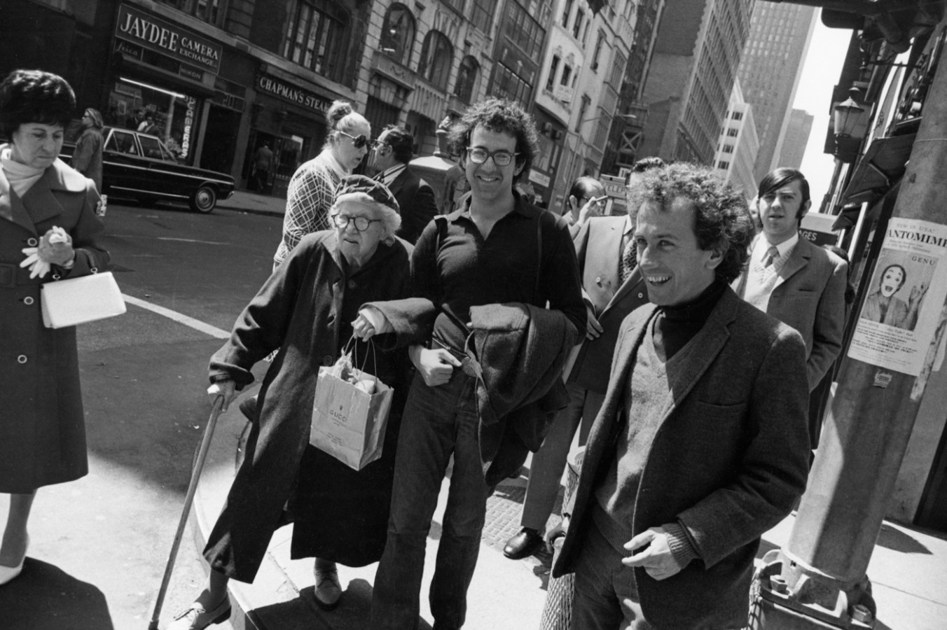 Black-and-white photograph of two smiling men with curly hair accompanying an elderly woman about to cross the street