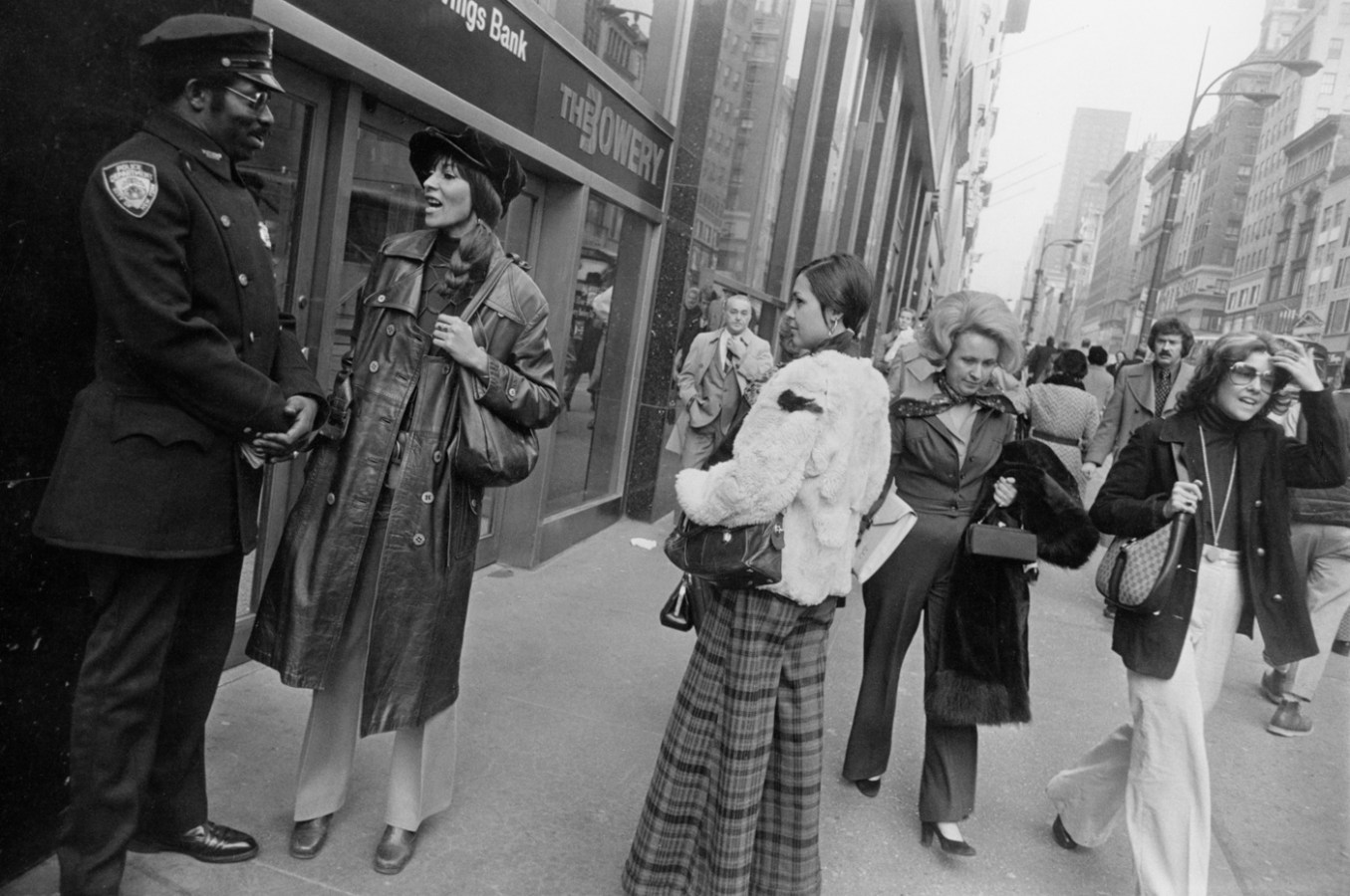 Black-and-white photograph of two young women pausing on a busy city sidewalk to talk to a police officer