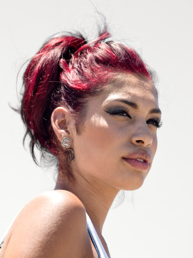 Color photographic portrait of a young woman with dyed red hair in a bun in front of a blank white wall
