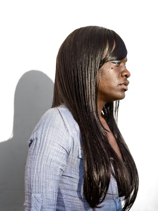 Color photographic portrait of a young woman with long straightened hair in profile against a blank white wall