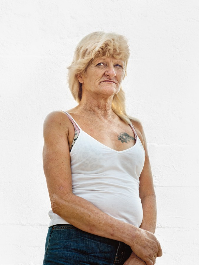 Color photographic portrait of a middle-aged woman in a white tank top standing in front of a blank white wall