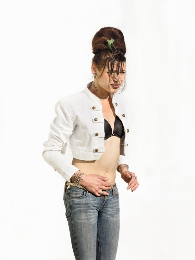 Color photographic portrait of a woman wearing a cropped jacket and jeans standing in front of a blank white wall