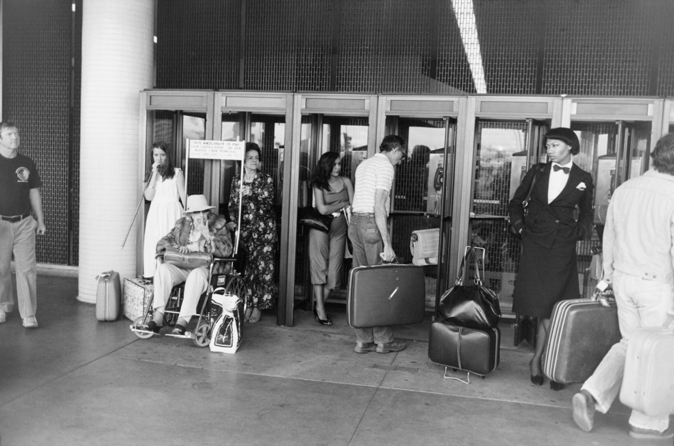 Black-and-white photograph of travelers with their suitcases outside a set of glass doors
