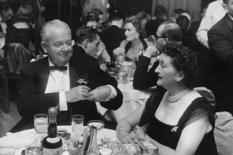 Black-and-white photograph of an older man and woman in formal dress conversing at a round table