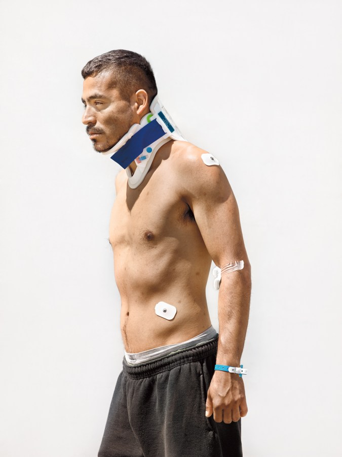 Color photographic portrait of a shirtless man in a neck brace standing in front of a blank white wall