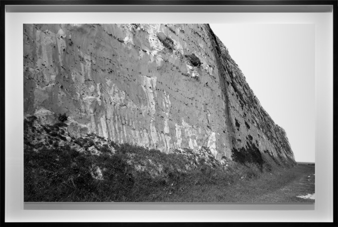 Black-and-white photograph of the base of a bare pale cliff face
