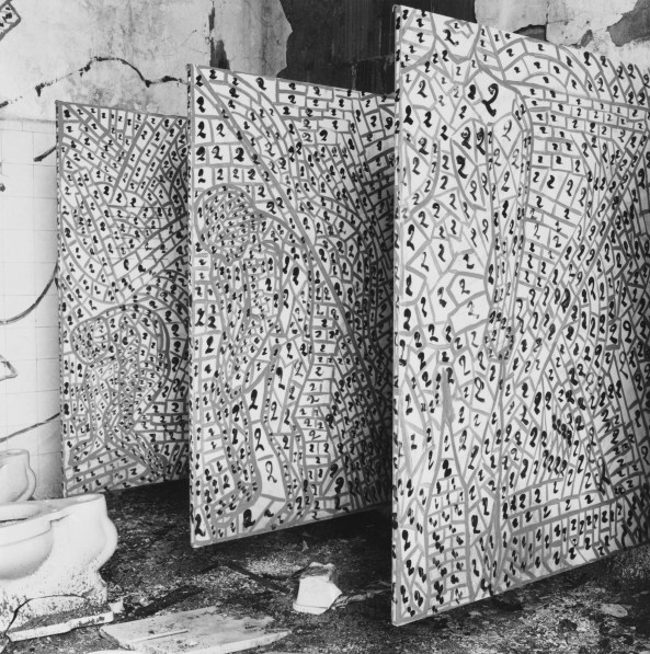 Black-and-white photograph of three painted panels standing in a derelict tiled bathroom