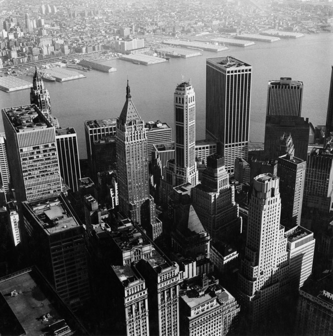 Black-and-white photograph of city high-rise buildings along a waterfront with piers on the opposite shore