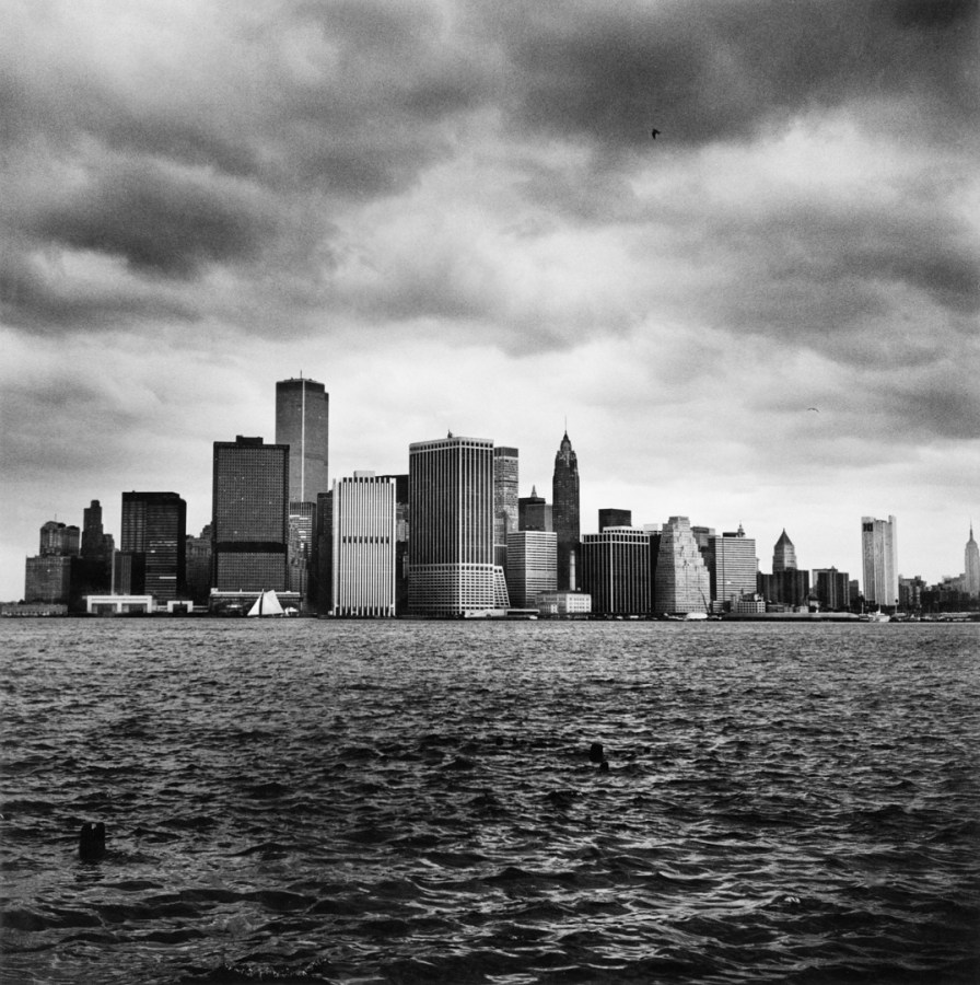 Black-and-white photograph of a city skyline from a river under a cloudy sky