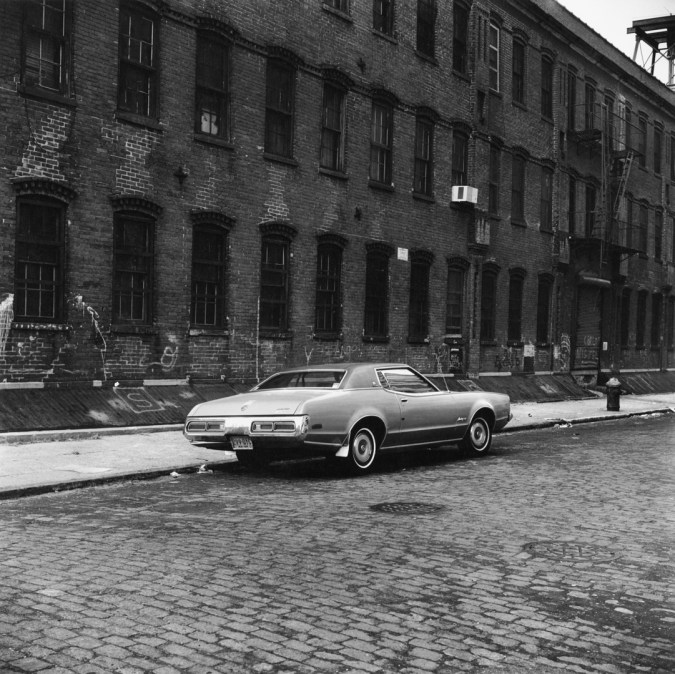 Black-and-white photograph of a car parked on a cobbled street next to a brick building