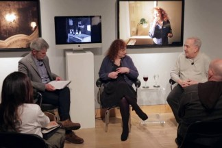 Video still of a group of people seated in a gallery during a panel discussion