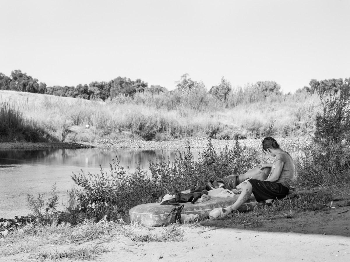 Black-and-white photograph of two people reclining on a bare mattress on a riverbank in the shade