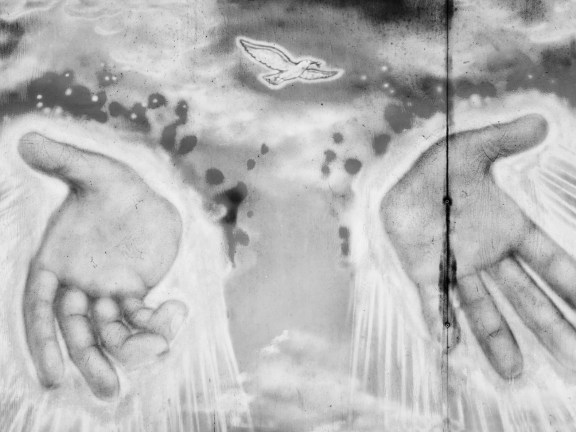 Black-and-white photograph of a wall painting of a flying dove and two hands emanating rays of light