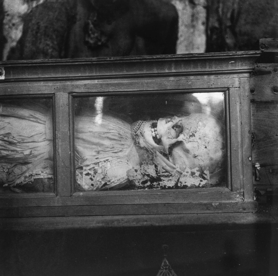 Black-and-white photograph of a skeleton in a lace dress lying in a glass-fronted box