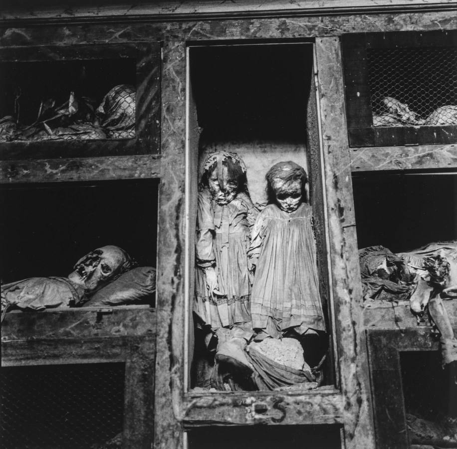 Black-and-white photograph of two preserved children's bodies propped up in a wooden compartment amid other bodies