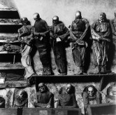 Black-and-white photograph of preserved skeletons dressed in shrouds and gowns in two rows