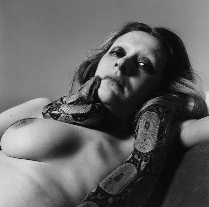 Black-and-white photograph of a reclining nude woman with a python around her neck