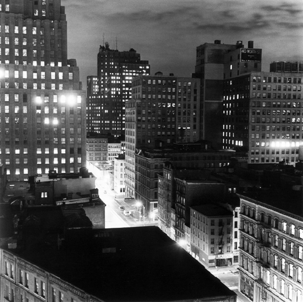 Black-and-white photograph of city buildings with lighted windows above a glowing street