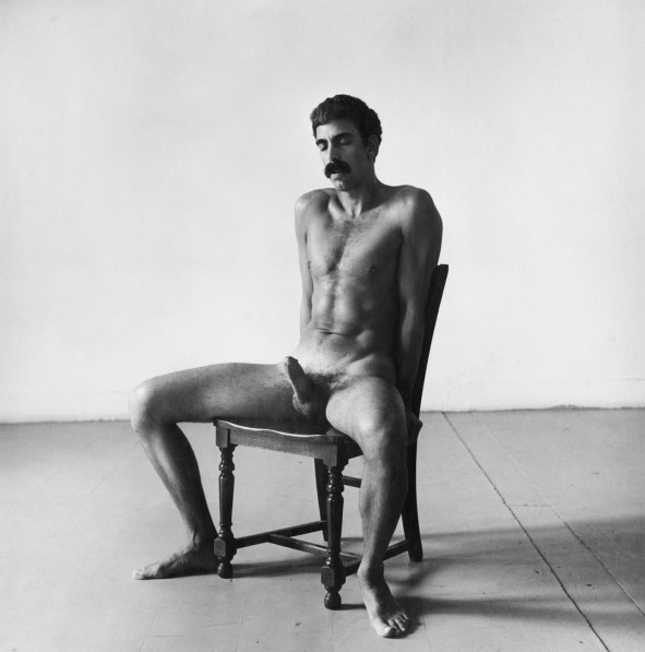 Black-and-white photograph of a seated nude man with an erection and his hands behind his back