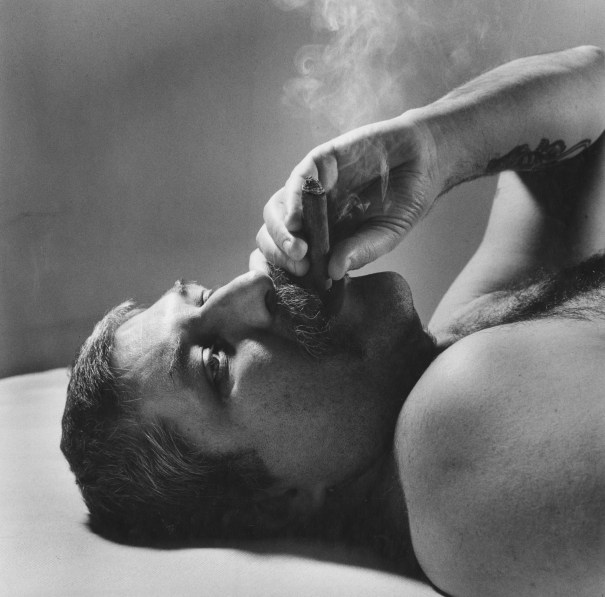 Black-and-white photograph of a man smoking a cigar while lying down