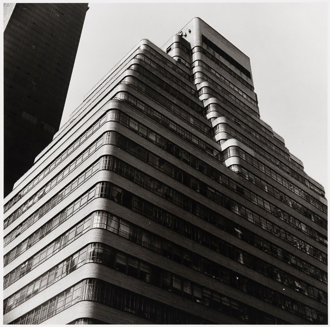 Black-and-white photograph from below of a stepped building with rounded corners