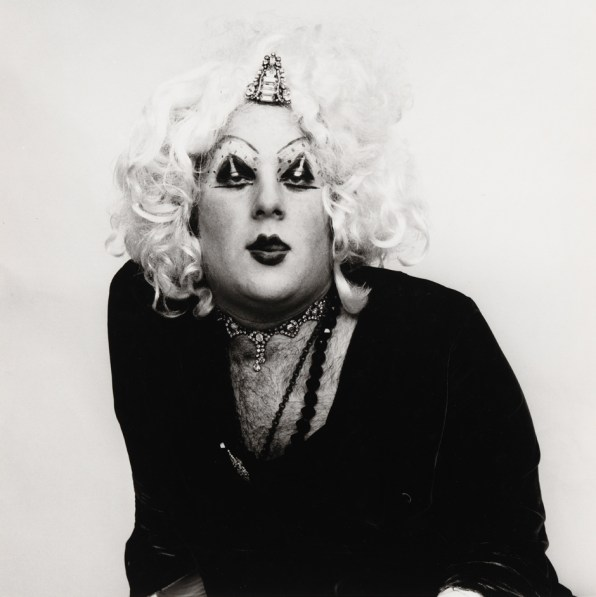 Black-and-white photograph of a man with heavy jewelry and makeup wearing a curly blond wig