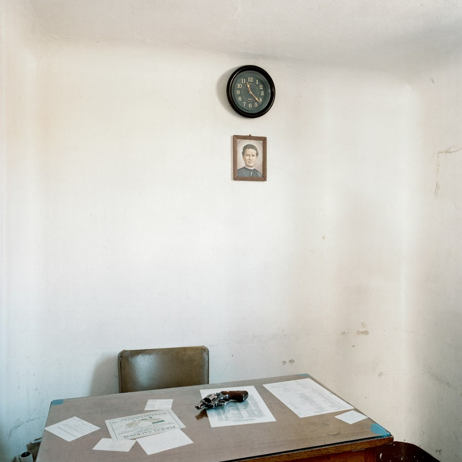 Color photograph of a desk with scattered papers and a gun against a white wall bare except for a clock and a small portrait