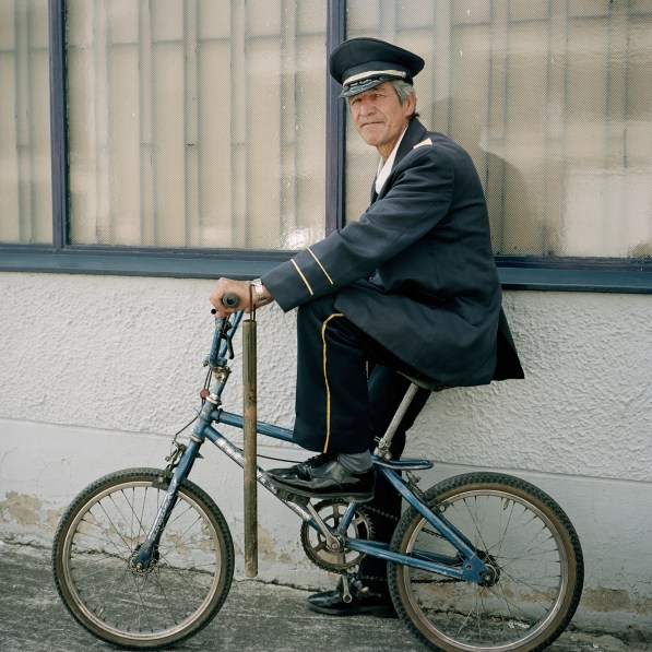 Color photographic portrait of a man in navy blue cap and uniform on a child-sized bicycle carrying a baton