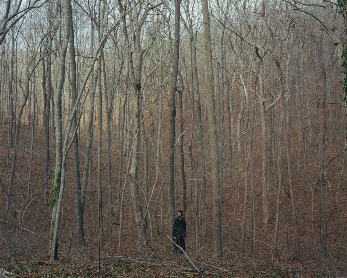 Color photograph of a lone figure dressed in black standing amidst bare trees on a brown hillside