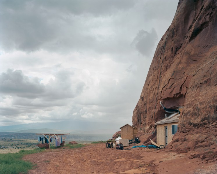 Color photograph of a house built into the side of a red cliff-face with a clothesline out front overlooking a flat valley
