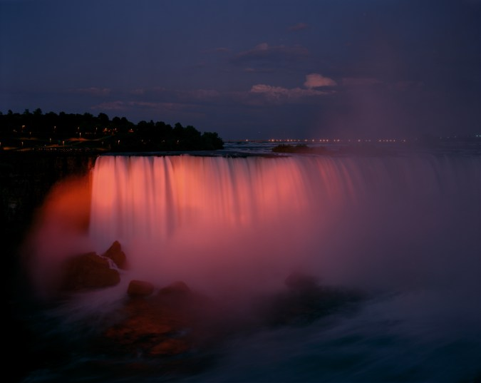 Color photograph of the Niagara falls at sunset, bathed in pink light