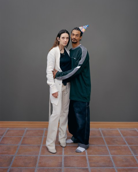 Color photograph of a standing couple against a bare gray wall