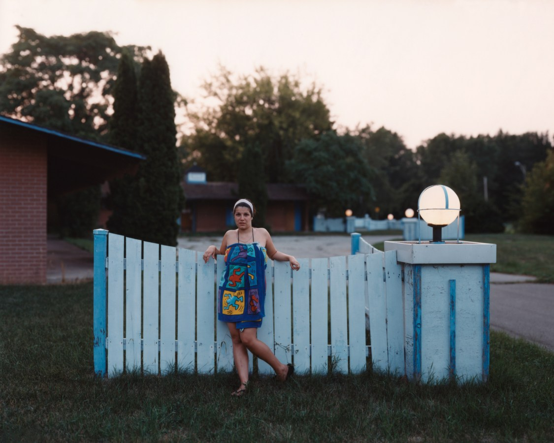 Color photograph of a woman wrapped in brightly patterned towel leaning against a blue fence