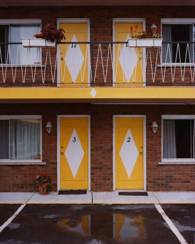 Color photograph of four yellow motel doors across two floors, with a white diamond and room number painted on each
