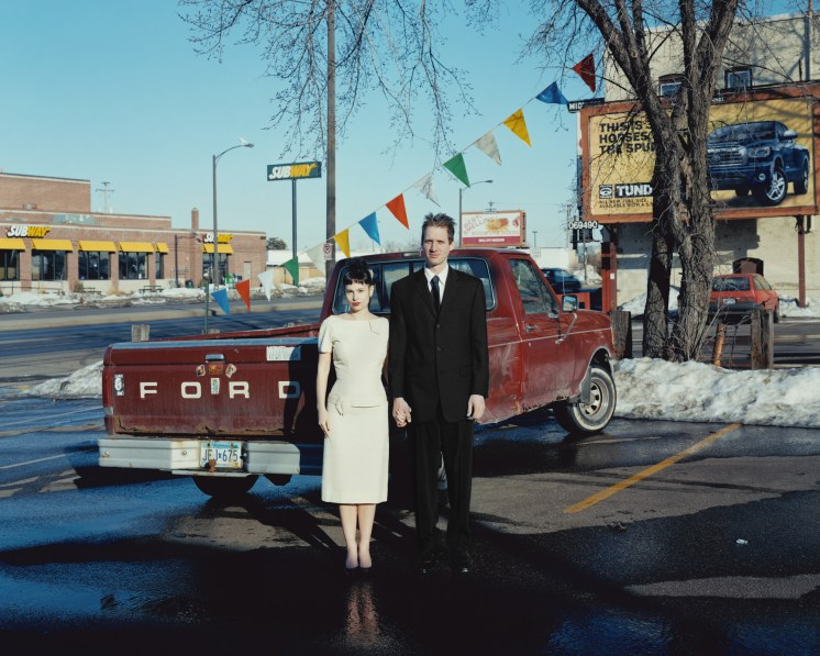Color photograph of a woman in a white dress and a man in a black suit standing in front of a red Ford pickup truck in a parking lot