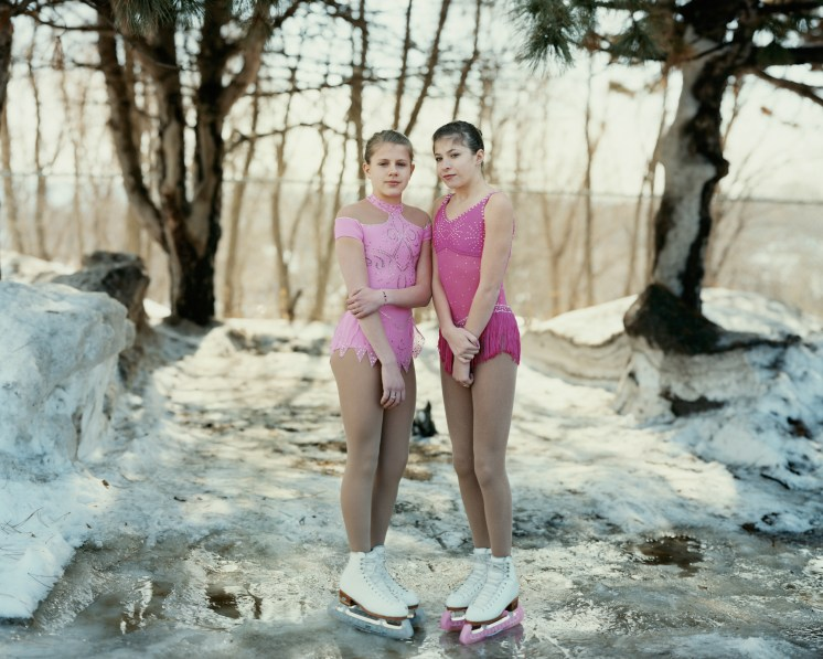 Color photograph of two teenage girls wearing ice skates and pink leotards standing at the edge of a frozen pond in front of bare trees