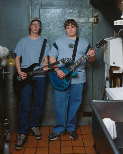 Color photograph of two teenage boys both dressed in blue holding electric guitars while standing in a commercial kitchen setting