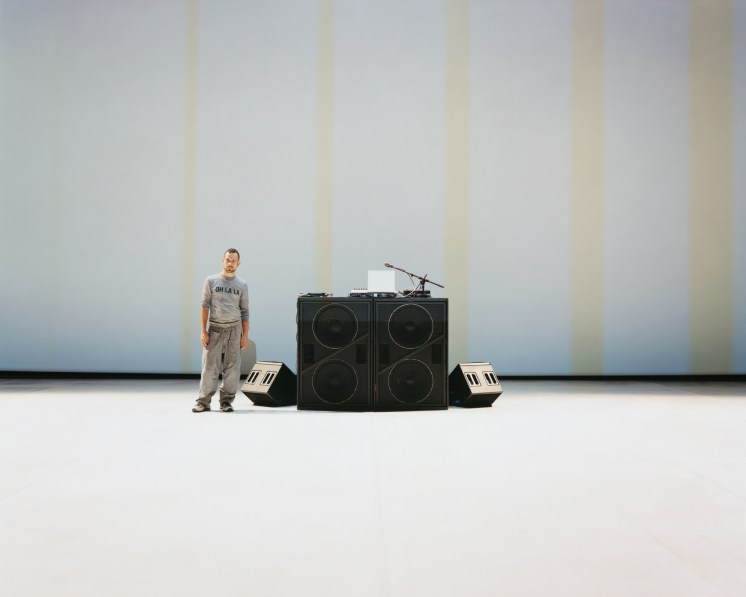 Color photograph of a man standing next to a DJ's stand in front of a white wall with faint yellow stripes