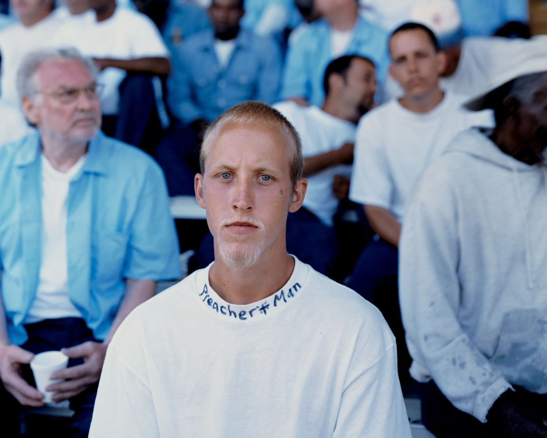 Color photograph of a young man wearing a white t-shirt with PREACHER MAN written in marker on the collar
