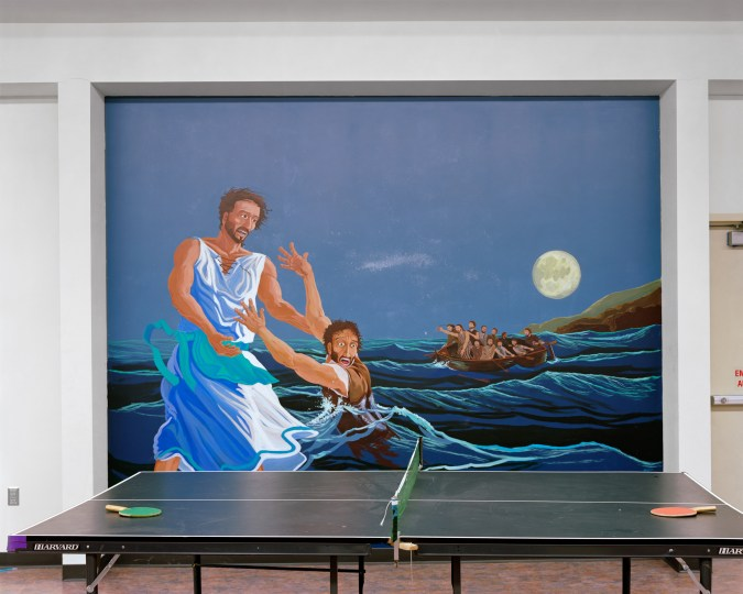 Color photograph of a ping pong table in front of a mural of a man reaching out of the sea to another dressed in white walking on water