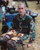 Color photographic portrait of a young man with a shaved head dressed in a camouflage military uniform with two peanut butter and jelly sandwiches on his lap