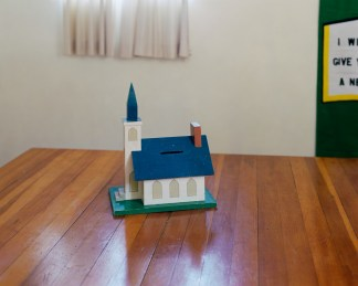 Color photograph of a simple model of a church sitting on a wooden table