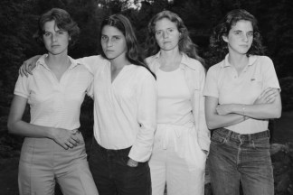 Black and white photograph of four young woman standing shoulder to shoulder in a backyard