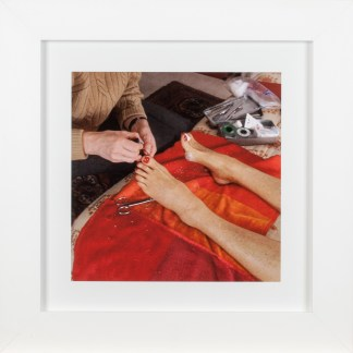 A square framed photograph of a woman's feet being pedicured over a bright orange towel
